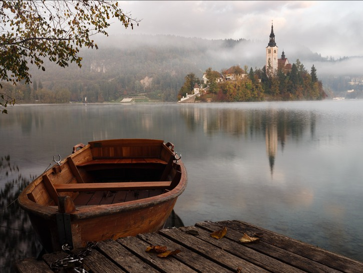 Rowboat moored to dock on Lake Bled, Slovenia, with island and church in the background