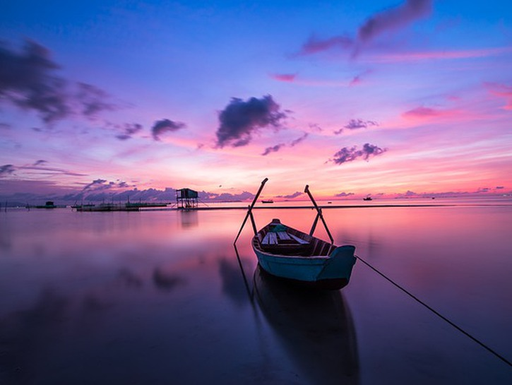 Rowoboat tied to dock in the water at sunset, Phu Quoc