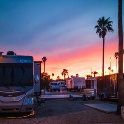 RV campers in front of sunset with palm trees