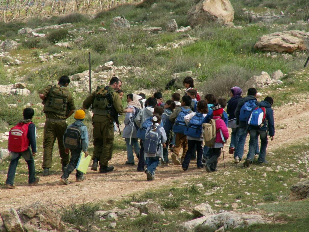 School kids being escorted to school by Israeli soldiers.