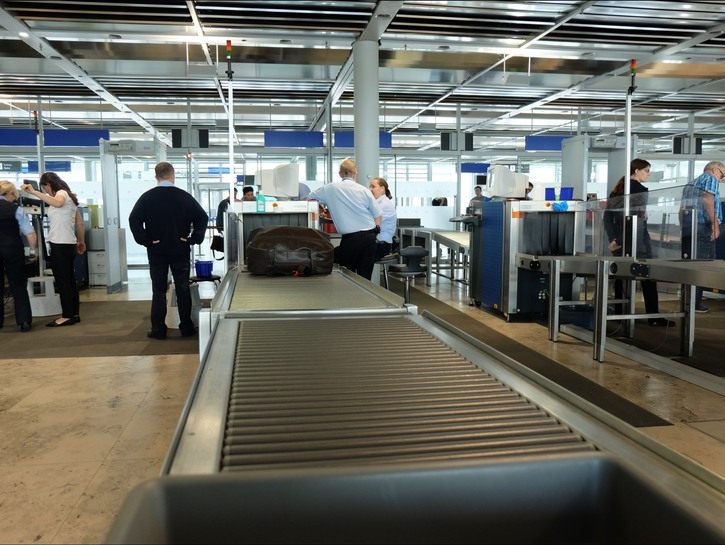 Security personnel stand around airport conveyer belt