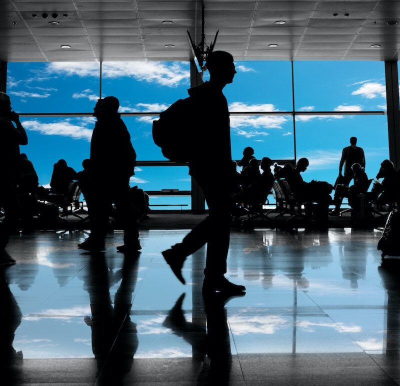 Silhouettes in a busy airport.