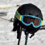 ski googles on ski helmet on ski poles on mountain