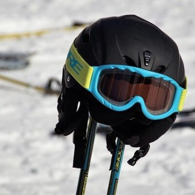ski googles on ski helmet on ski poles on mountain