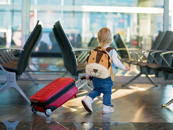 small child walking with backpack and suitcase