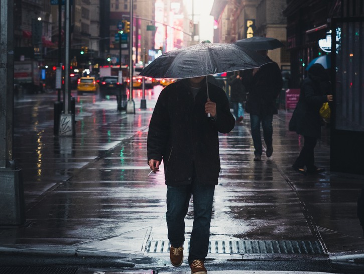 Smoking man with umbrella in the city