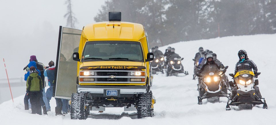 snow yacht and snow mobiles leading tourists through snowy yellowstone national park