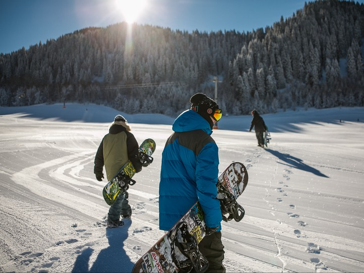 Snowboarders walking across level ground