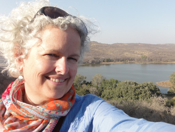 Solo travel writer Janice Waugh with lake and landscape in background