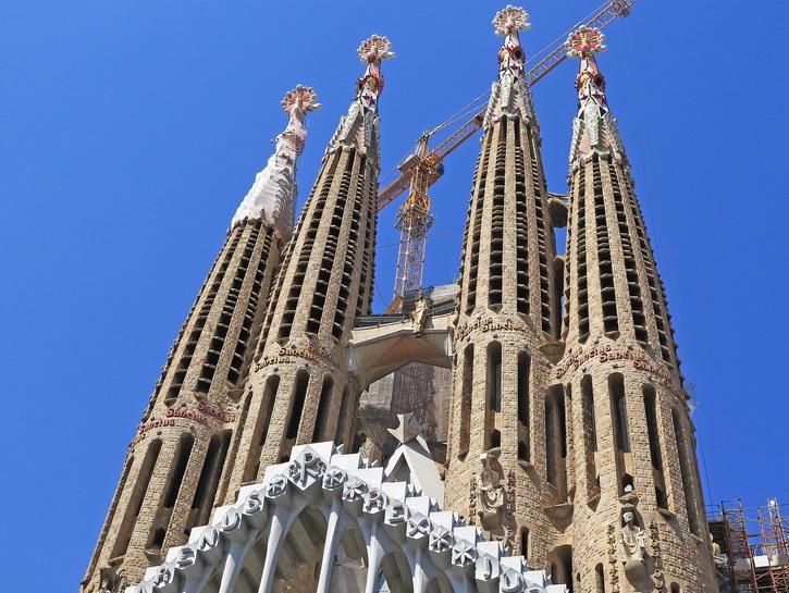 Spires of Sagrada Família Church with cranes.