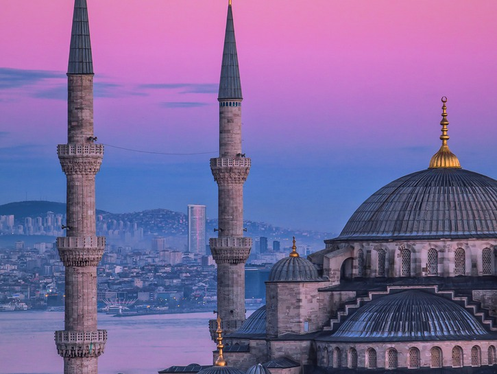 Spires of the Hagia Sophia at sunset, with Istanbul in the background