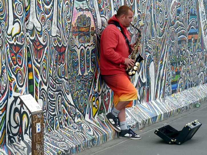 Street musician in front of street art, Berlin