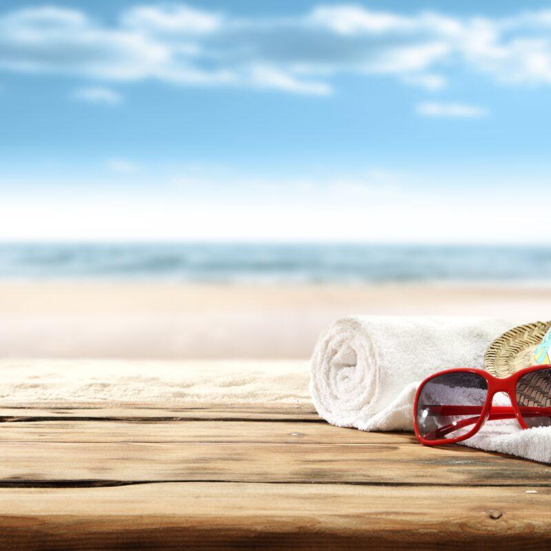 sunglasses, beach towel, beach hat, on beach porch