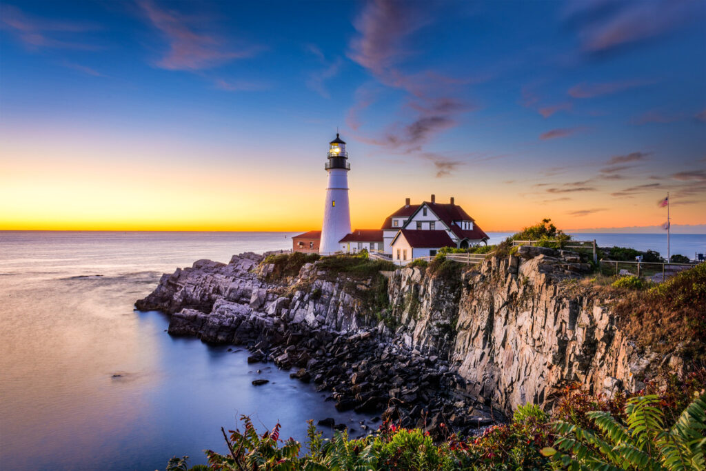 Sunset behind a lighthouse in Portland, Maine.