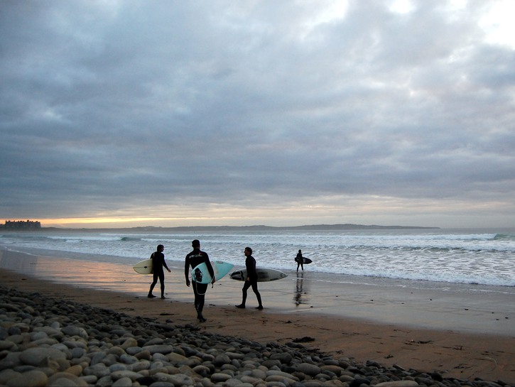 Surfers on the beach at sundown in Lahinch, Ireland.