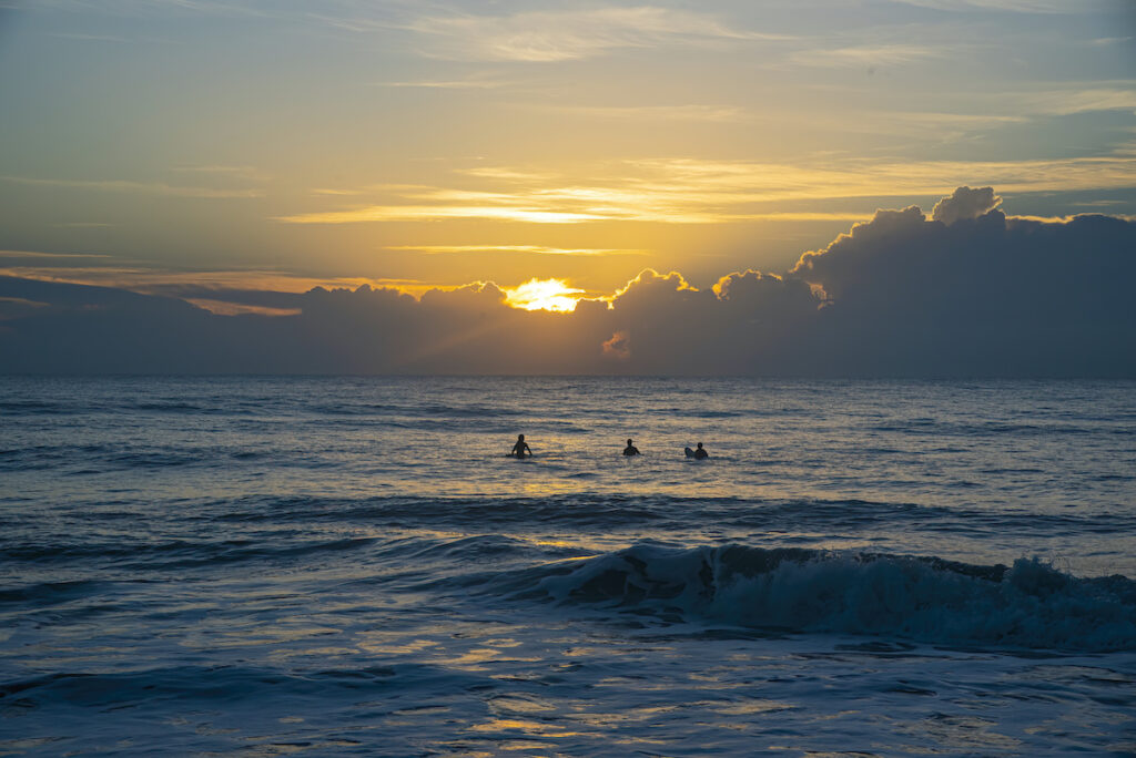 Surfers on the waves at dawn in Cocoa Beach, Florida.