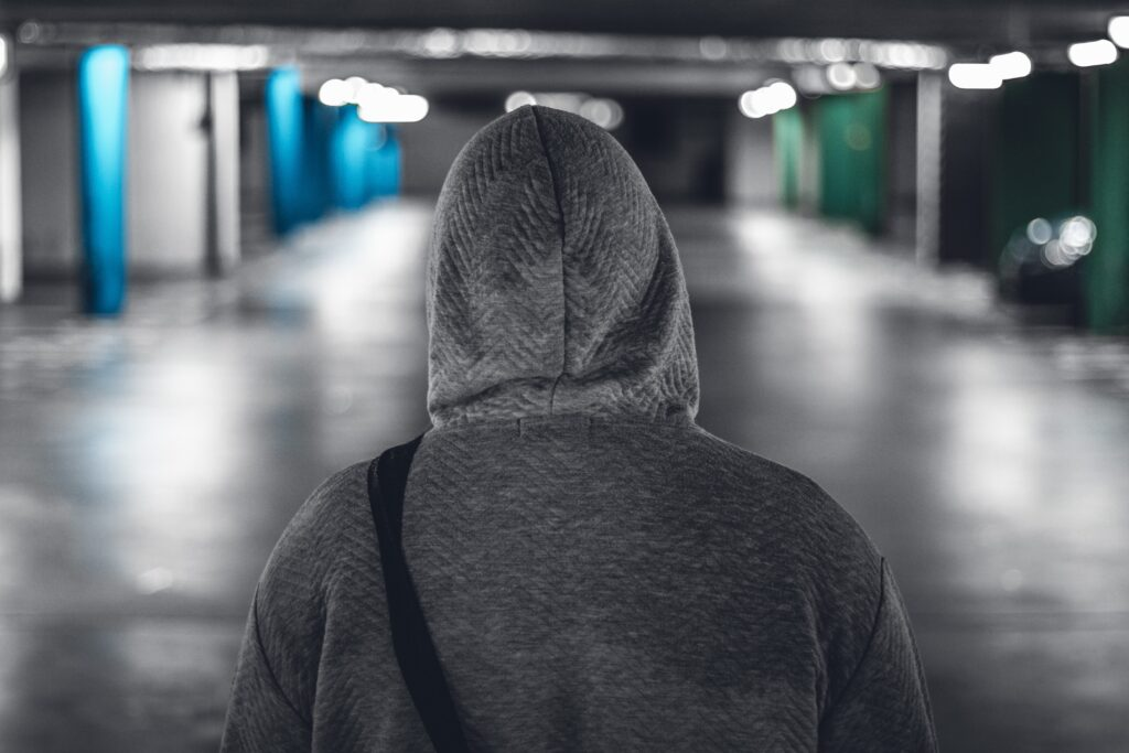 The back of a person wearing a gray hoodie with the hood pulled up