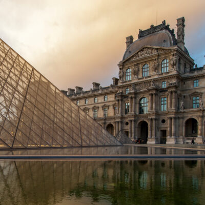 The exterior of the Louvre at sunset.