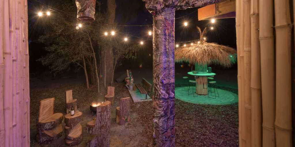 The fire pit and tiki hut at the treehouse Airbnb in Florida.