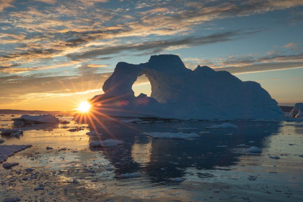 The midnight sun behind icebergs in Greenland.