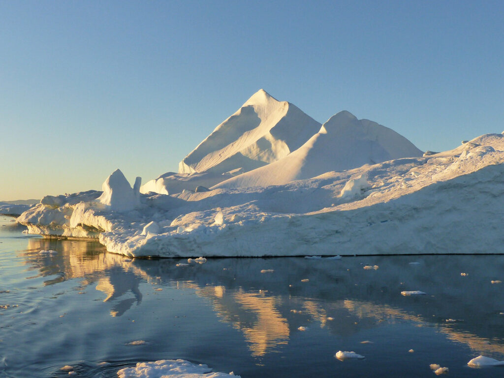 The midnight sun shining on an iceberg in Greenland.
