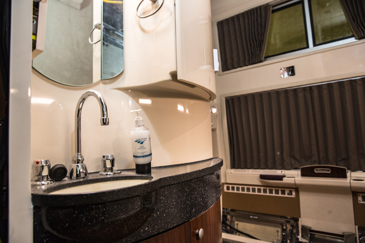 The small but stylish vanity of an Amtrak sleeper car train, including a sink, soap dispenser, cupbo