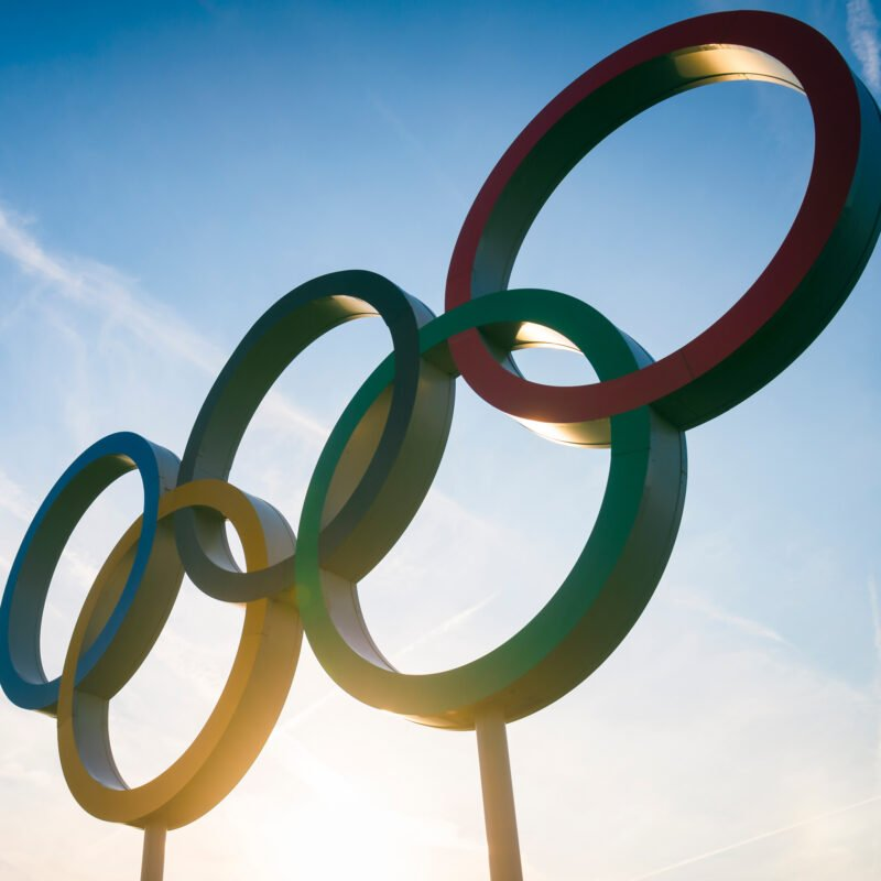 The sun shining behind the Olympic rings.
