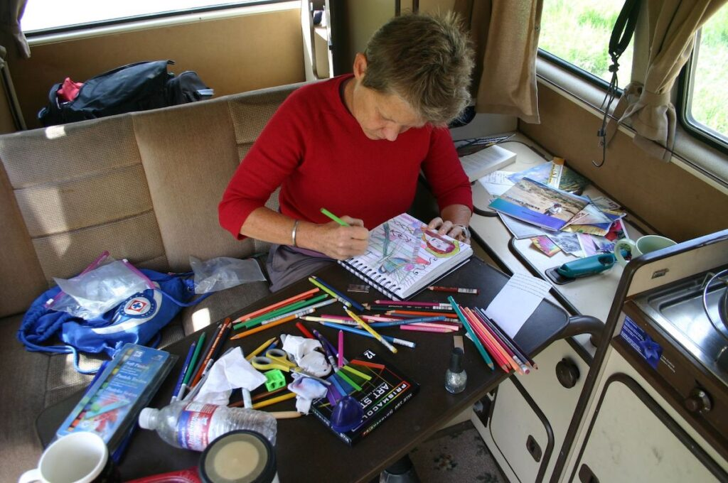 The writer drawing in the van.