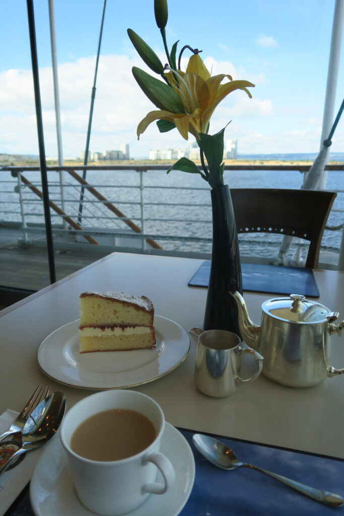 The writer enjoying tea on board the Royal Yacht Britannia.