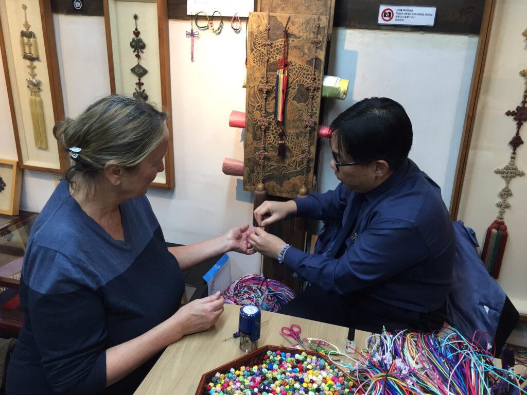 The writer making a bracelet in Seoul.