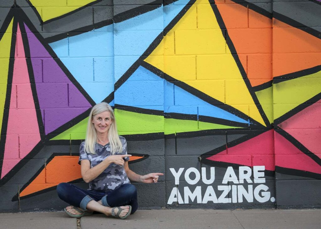 The writer next to a mural in Phoenix, Arizona.