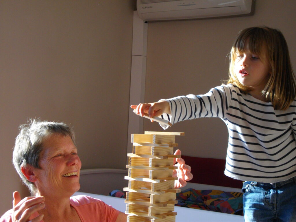 The writer playing Jenga with a family of new friends.