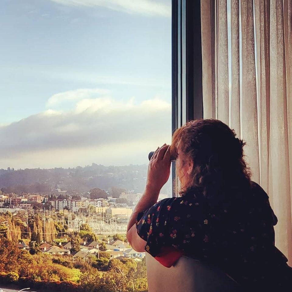 The writer using binoculars at the Grand Hyatt hotel.