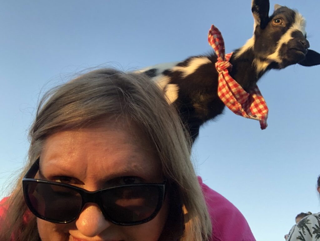 The writer with a goat on her back.