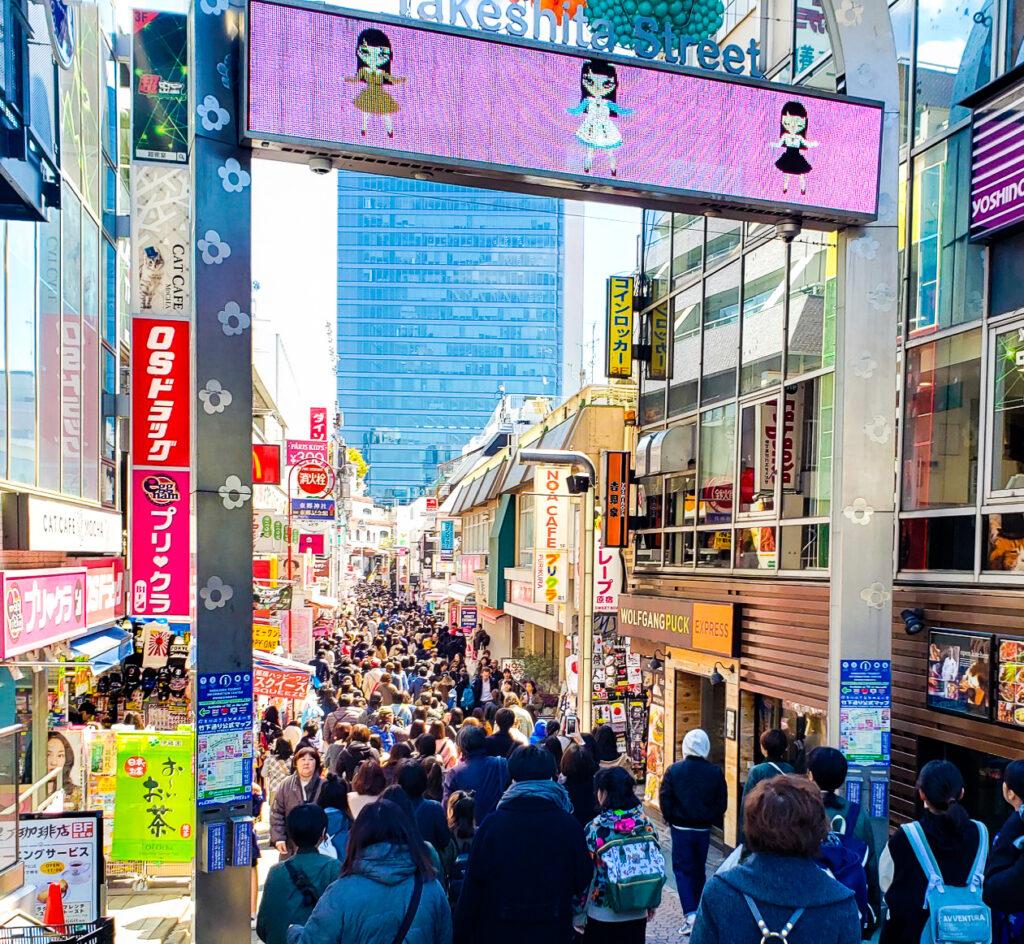 Tourists entering Takeshita Street in Tokyo.