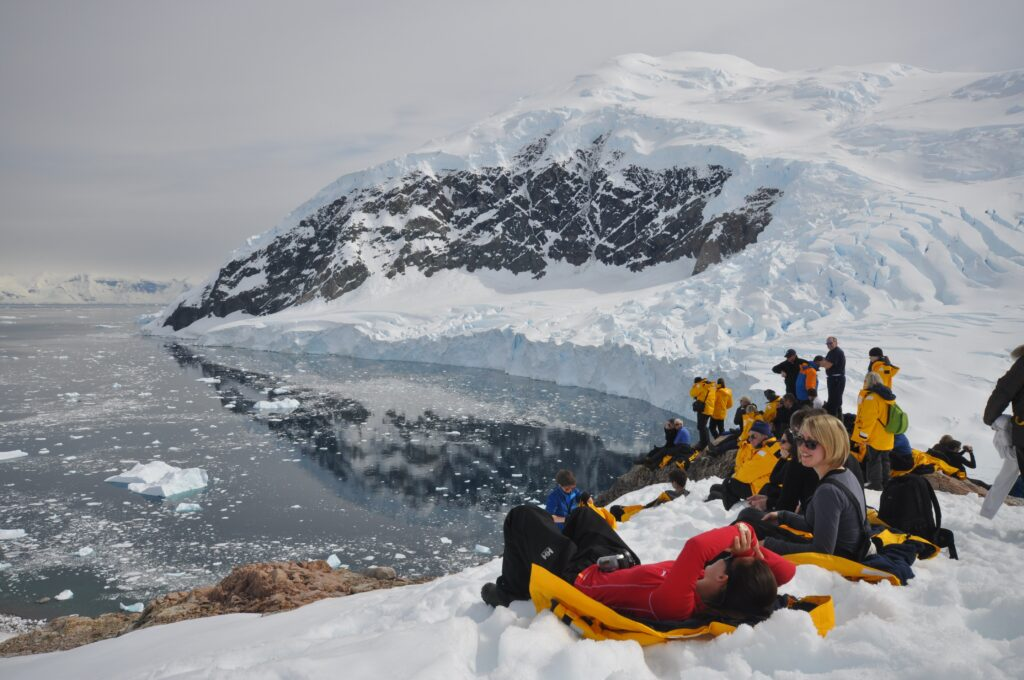 Tourists relaxing in the Antarctic snow, looking at the water
