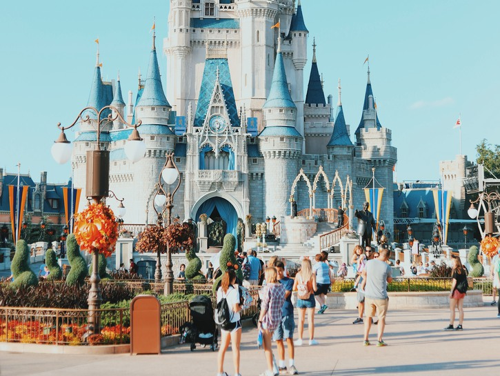 Tourists walk on street in front of Disney World castle