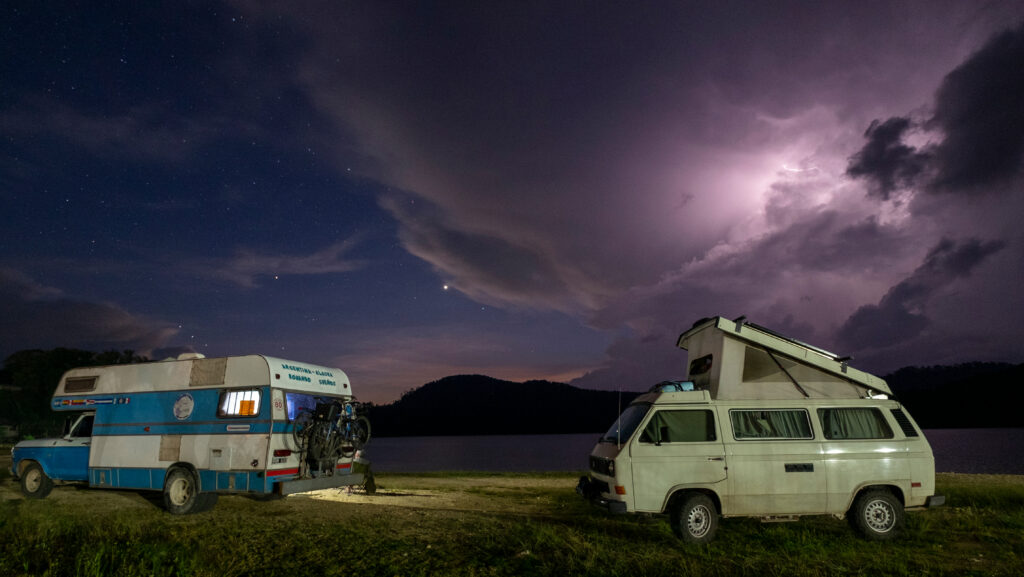 Two camper vans parked at night during a lightning storm near Lake Tziscao, Chiapas, Mexico
