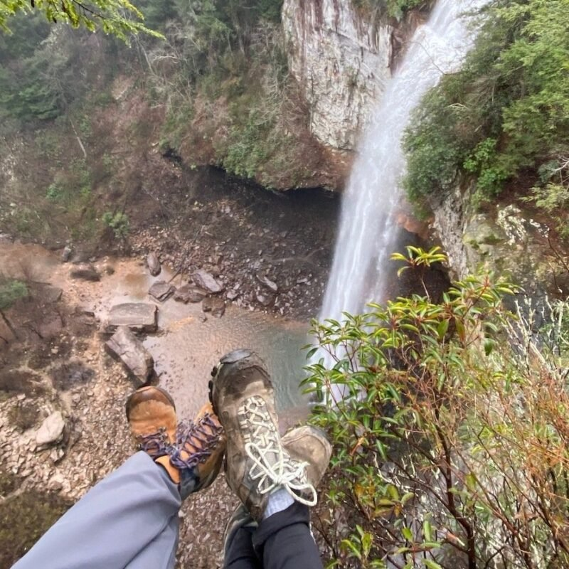 Two hikers facing a waterfall.