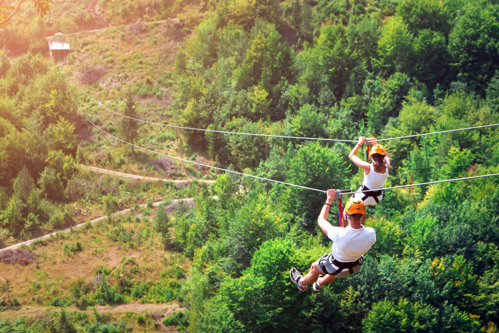Two people riding a zip line