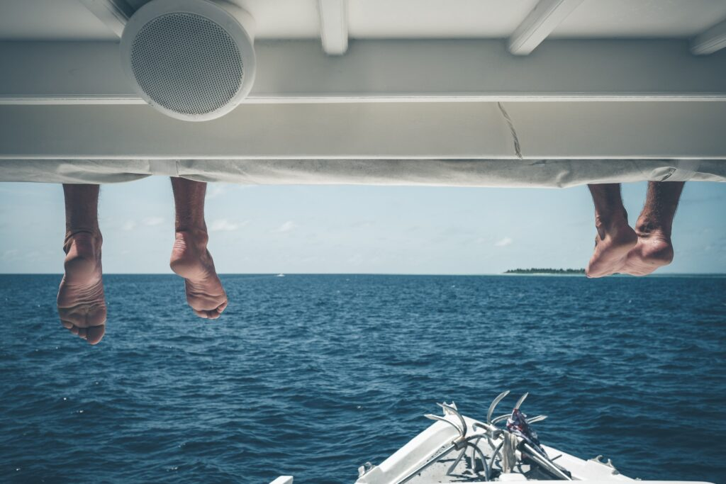 Two sets of feet hanging over the edge of a boat as vacationers relax in the waters just off Thaa At