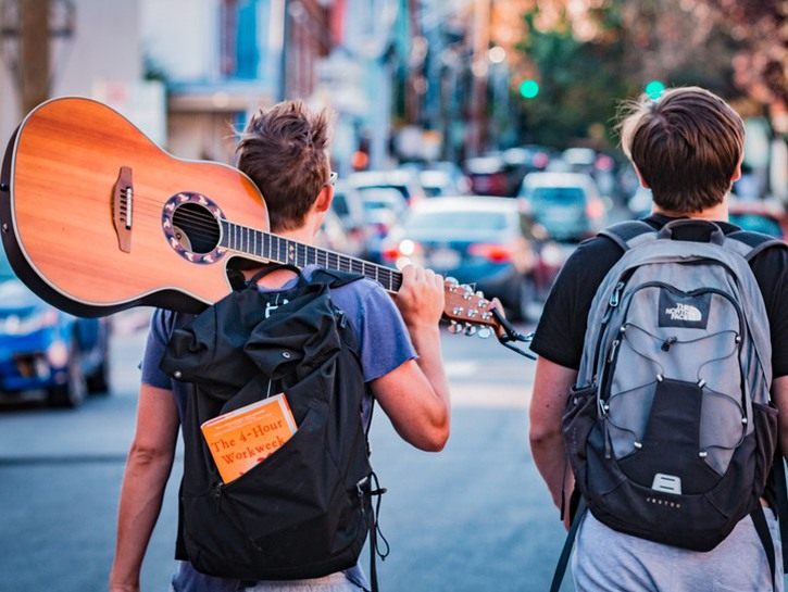 Two young backpackers walk along an urban street, one is carrying a guitar.