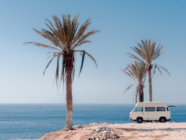 Van parked near beach under palm trees, Morocco