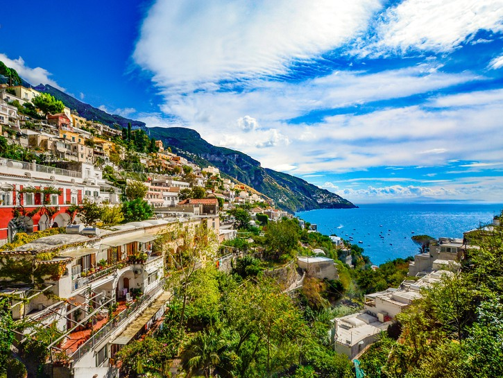 View across narrow valley to the sea, lined with colorful buildings, Positano, Italy