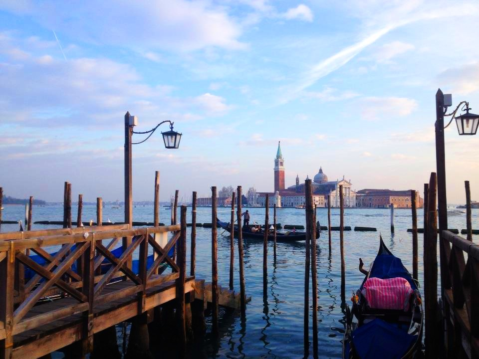 View of Venice from nearby island, piers and gondolas in the foreground
