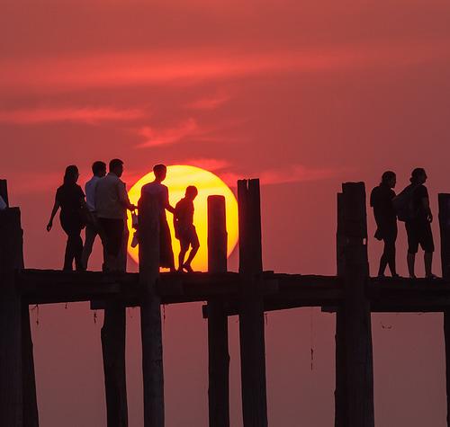 Villagers walk across U Bein Bridge silhouetted by the sun, Myanmar
