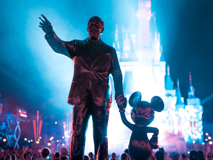 Walt Disney and Mickey Mouse in front of illuminated Castle, Disney World.
