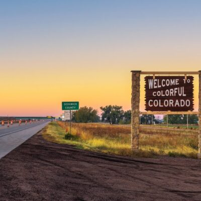 Welcome to Colorful Colorado sign in front of sunset