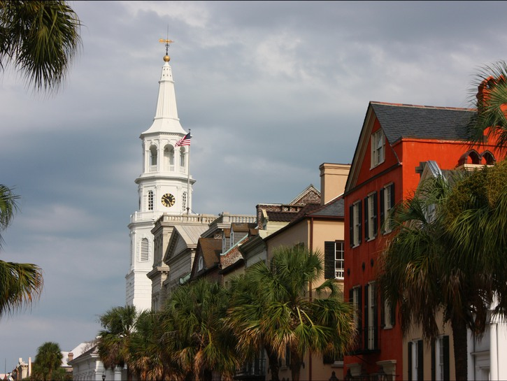 White church spire, palm trees, colorful old houses, Charleston SC