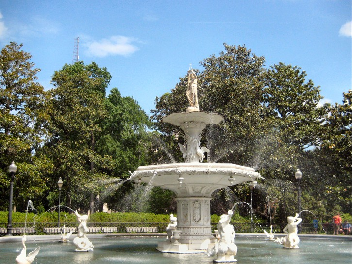 White marble water fountain with statues shooting water surrounded by shrubs, Forsyth Park, Savannah